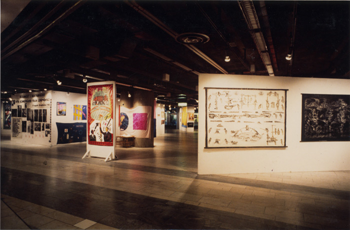 "Kulturhuset, The New from Leningrad 1988,general view of the exhbition.. In the middle, mounted on a square column, ""YA-YA"" by Evgenij Kozlov. On the right paitings by Evgenij Yufit."