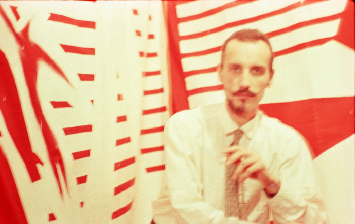 (E-E) Evgenij Kozlov at his flat and studio Galaxy Gallery, Peterhof (Leningrad), 1987 Left: Звезда. 6 Фигур / Star. 6 Figures, white paint on red calico, 211 x 230 cm, 1987 Right: Звезда / Star, white paint on red calico, 207 x 225 cm, 1987 Photo: Andrey Fitenko, Archive (E-E) Evgenij Kozlov